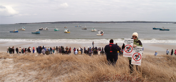 View of the rally participants on the beach with lobster boats offshore